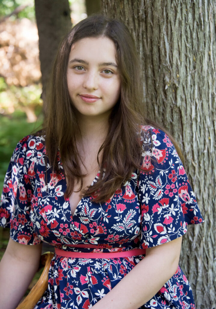 Image Description: Izzy is wearing a blue dress with pink and white flowers and leaves.  She is looking straight at the camera with a slight smile and sitting in front of some trees.