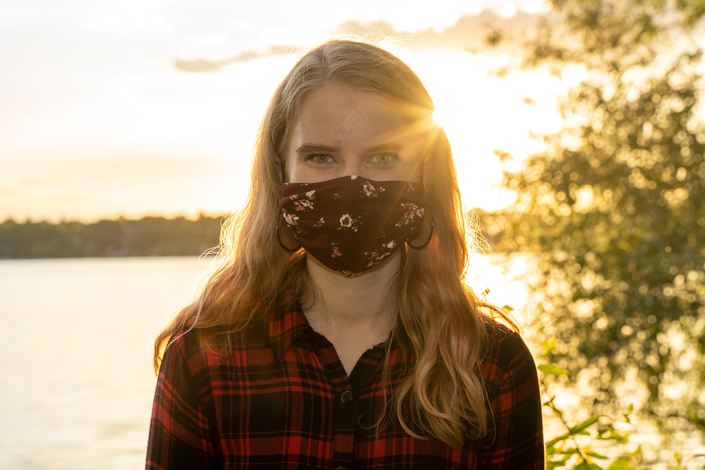 Image Description: Eleanor is wearing a red and black plaid flannel shirt and a burgundy mask with light pink flowers on it.  She is looking straight at the camera and standing in front of a lake.