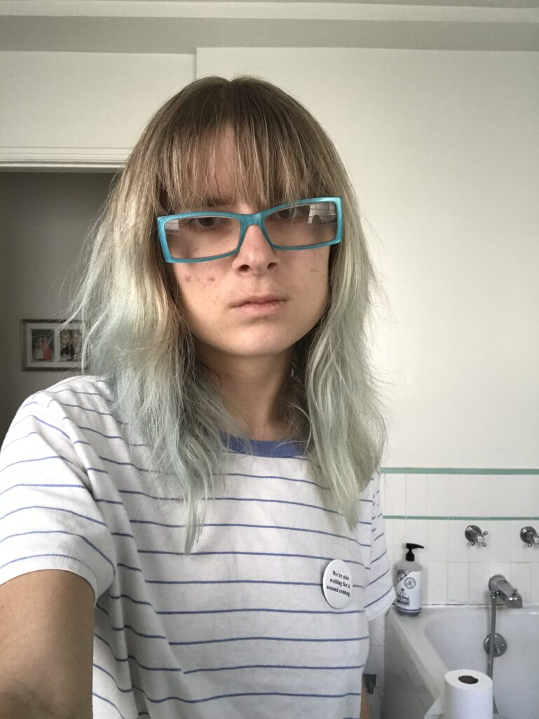 Image Description: Z wearing a white t-shirt with blue horizontal stripes.  She is holding the camera with her hand and looking straight at the camera with a straight face.